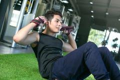 Homme asiatique de sport établissant son ABS dans un gymnase Photographie stock
