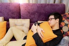 Homme asiatique dormant sur le safa dans la chambre de home cinéma photographie stock libre de droits