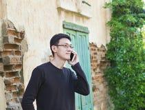 Homme asiatique employant l'outsite de smartphone dans la vieille ville photos libres de droits