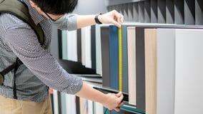 Homme asiatique employant le ruban métrique sur des matériaux de coffret photo stock
