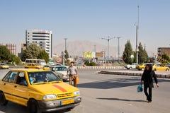 Homme asiatique et femme essayant d'attraper le taxi sur la route à grand trafic photographie stock