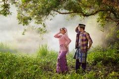 Homme asiatique et femme musulmans portant la robe traditionnelle Photo stock