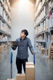 Homme asiatique faisant l'inventaire sur le comprim? dans l'entrep?t photos stock
