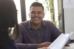 Homme asiatique heureux attirant parlant avec son collègue à l'intérieur au milieu du jour occupé au bureau images stock