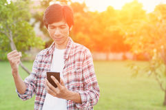 Homme asiatique heureux avec les actualités ou le message du téléphone intelligent Photo libre de droits