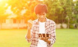 Homme asiatique heureux avec les actualités ou le message du téléphone intelligent dans le jardin, Images stock