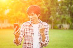 Homme asiatique heureux avec les actualités ou le message du téléphone intelligent dans le jardin, Photographie stock