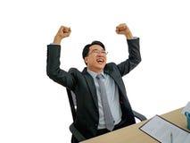 Homme asiatique heureux d'affaires s'asseyant sur son bureau sur le backgro d'isolement photographie stock