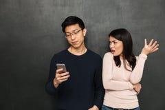 Homme asiatique heureux dans des lunettes utilisant son smartphone Photographie stock