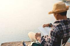 Homme asiatique heureux de hippie lisant un livre à l'arrière-plan de nature Photo libre de droits