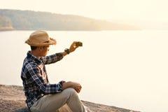Homme asiatique heureux de hippie tenant l'appareil-photo à l'arrière-plan de nature Photos libres de droits