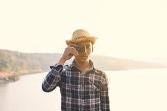Homme asiatique heureux de hippie tenant l'appareil-photo en nature Photographie stock libre de droits