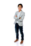 Homme asiatique heureux se tenant avec des bras pliés Image libre de droits