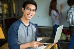 Homme asiatique heureux tenant l'ordinateur portable et étudiant avec des amis Photo stock