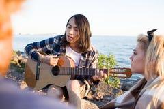 Homme asiatique jouant la guitare pendant la partie Photographie stock libre de droits