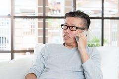 Homme asiatique mûr invitant le smartphone Images stock