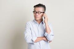 Homme asiatique mûr invitant le smartphone Image libre de droits