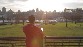 Homme asiatique marchant à son bourdon blanc - fond de parc de coucher du soleil clips vidéos