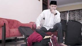 Homme asiatique musulman avec le songkok ou le chapeau principal se préparer au déplacement image stock