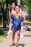 Homme asiatique portant son ferroutage d'amie pour le sport Images stock