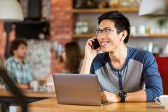 Homme asiatique positif à l'aide de l'ordinateur portable et parlant sur le téléphone portable Photographie stock libre de droits