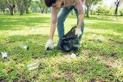 Homme asiatique prenant les déchets en plastique de ménage en parc photos libres de droits