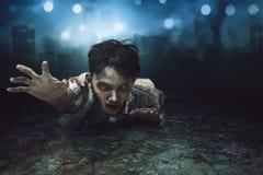 Homme asiatique rampant de zombi se couchant dessus avec le visage blessé photographie stock