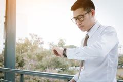 Homme asiatique sûr se tenant vérifiant le temps image libre de droits