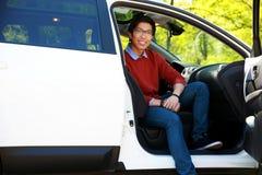 Homme asiatique s'asseyant dans la voiture Images stock