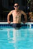 Homme asiatique se tenant dans la piscine avec des bras de côté Image libre de droits