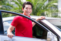 Homme asiatique se tenant devant la voiture Image stock