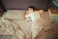 Homme asiatique souffrant de la dépression sur le lit images libres de droits