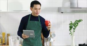 Homme asiatique utilisant la Tablette et boire du jus banque de vidéos