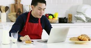 Homme asiatique utilisant la Tablette et manger un certain gâteau banque de vidéos