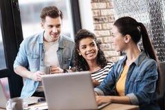 Homme aspirant et deux dames et travailler sur l'ordinateur portable Image stock