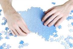 Homme assemblant le puzzle bleu Photographie stock libre de droits