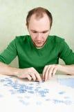 Homme assemblant les parties bleues de puzzle Photos libres de droits