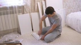 Homme assemblant les pièces en bois de meubles banque de vidéos