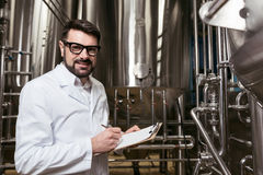 Homme assidu faisant des notes à l'usine de bière photos stock