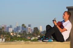 Homme assis jouant la guitare acoustique avec l'horizon de LA Photos libres de droits