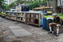 Homme assis près de la bande piétonnière Image stock