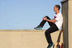 Homme assis sur le rebord examinant la distance avec la guitare Image libre de droits