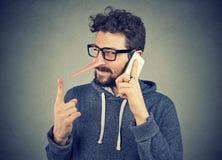 Homme astucieux de menteur avec le long nez parlant au téléphone portable photo libre de droits