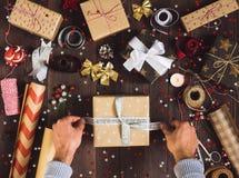 Homme attachant l'arc sur le processus de boîte-cadeau de Noël du boîte-cadeau de nouvelle année de paquet Photos stock