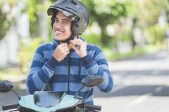 Homme attachant son casque de motocyclette images libres de droits