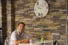 Homme attendant son petit déjeuner dans le cafétéria Photos stock