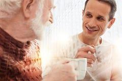 Homme attentif aimable regardant son père âgé tout en buvant du café Photo libre de droits