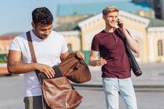 Homme attentif de brune mettant son comprimé dans le sac Photographie stock