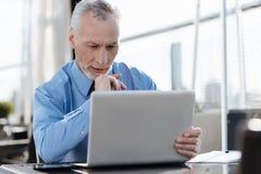 Homme attentif regardant son nouvel ordinateur portable Image libre de droits