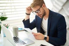 Homme attentif vérifiant des documents dans le bureau images stock